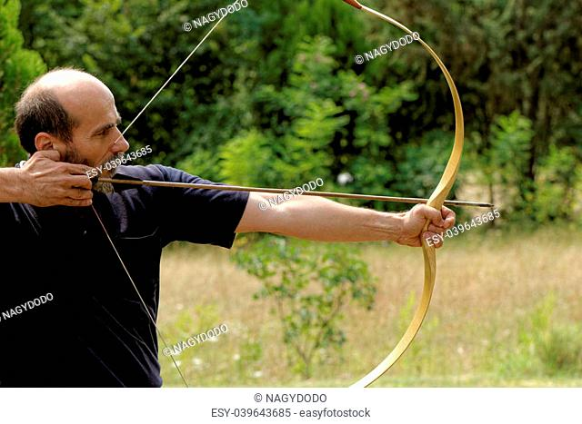 archery man shooting arrow with bow in the nature