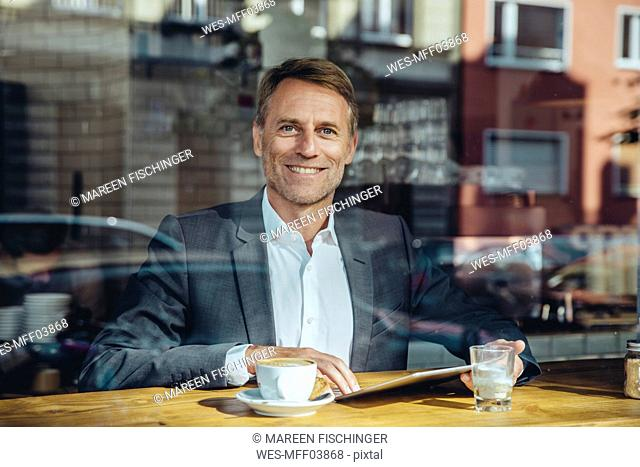 Portrait of smiling businessman with tablet in cafe