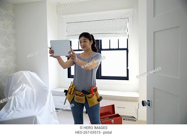 Woman researching DIY on digital tablet in bedroom