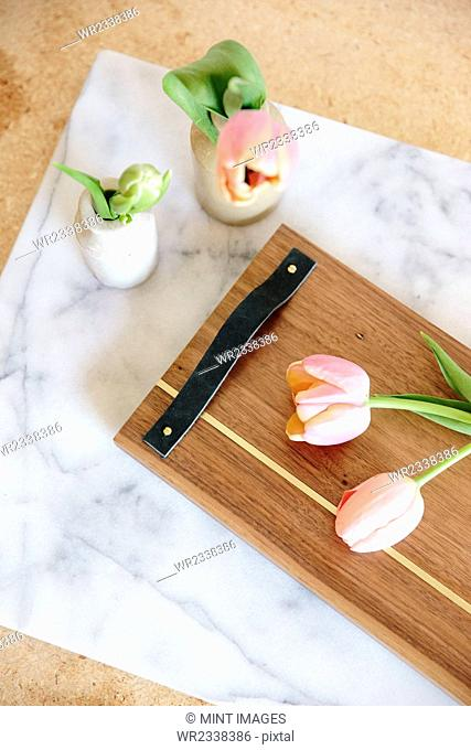 A marble slab with two vases and pink tulips and a wooden board with handle