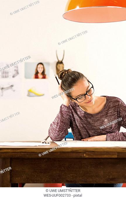 Young woman looking at her drawing at home