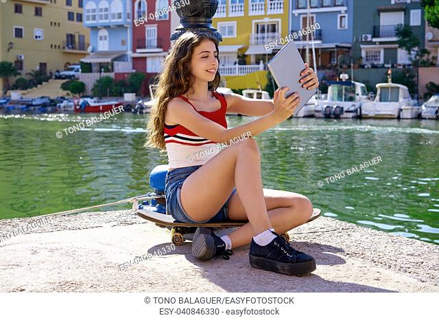 Girl teen with skateboard and tablet selfie playing with touch on marina