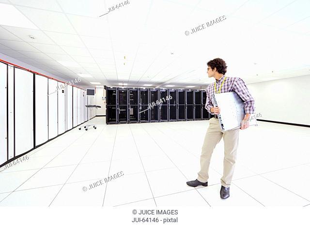 Technician holding server drive in server room