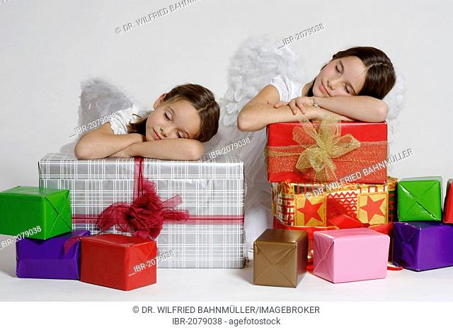 Two tired girls dressed up as Christmas angels with gifts, Christmas