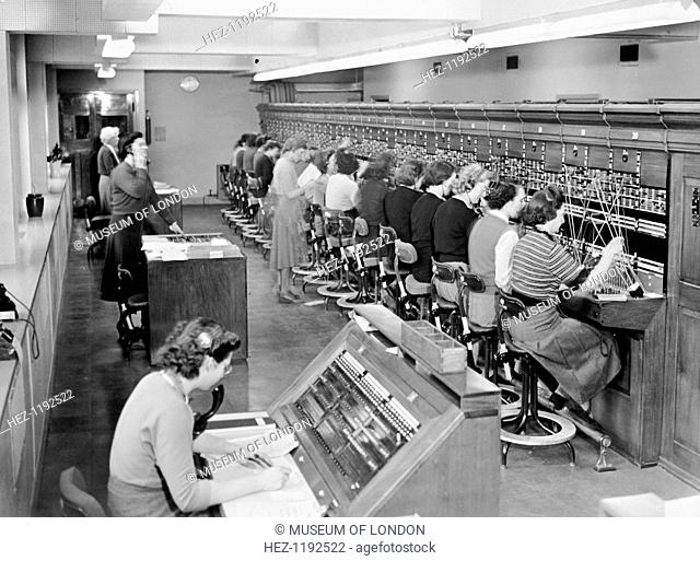 Telephone exchange at Cadley Hall, London, March 1951. Women telephonists at the switchboard