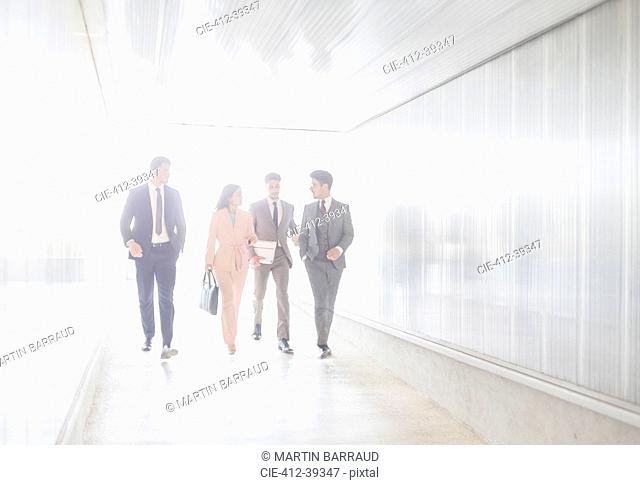 Business people talking and walking in office corridor
