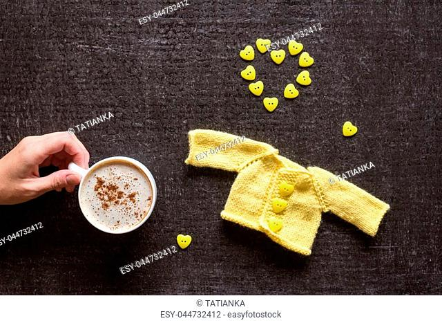 Cup of coffee, yellow knitted sweater for a doll and a heart made of buttons on a grunge black background. Female hand holding a cup