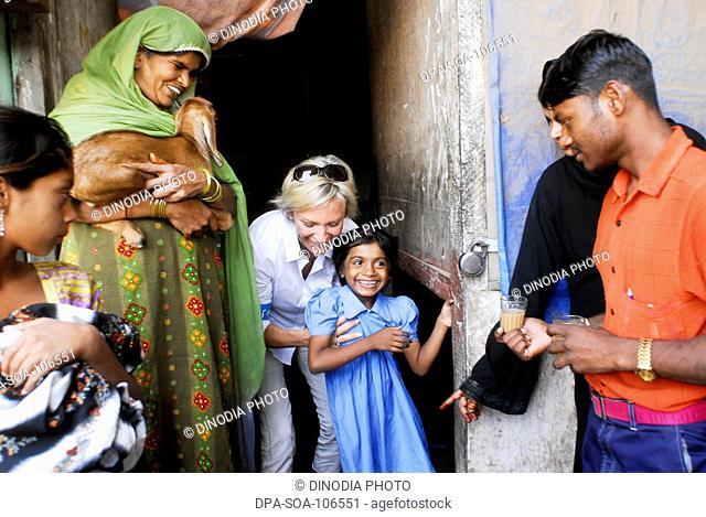Sabine Christiansen enjoying with girl at Amrae an NGO at Nehru Nagar ; Golibar Slum ;Santacruz ;Bombay Mumbai ; Maharashtra ; India NO MR