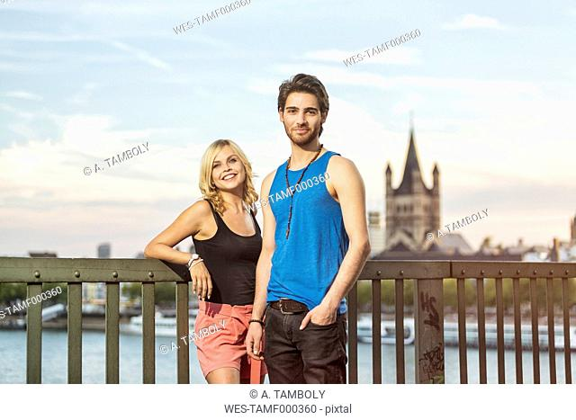 Germany, Cologne, happy young couple standing on Rhine Bridge