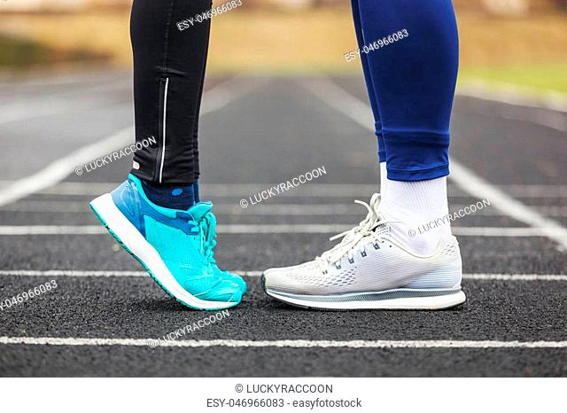 Cropped shot of a male and female legs in running shoes standing close to each other. Love concept image