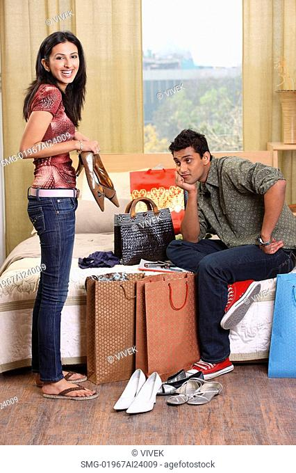 woman showing boyfriend her shopping purchases