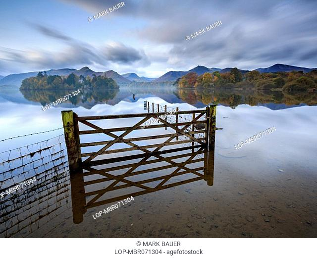 England, Cumbria, Keswick. A gate and fence in a flooded field by Derwent Water near Keswick