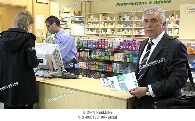 MS Portrait of consultant in pharmacy, client purchasing in background. Panning from left to right
