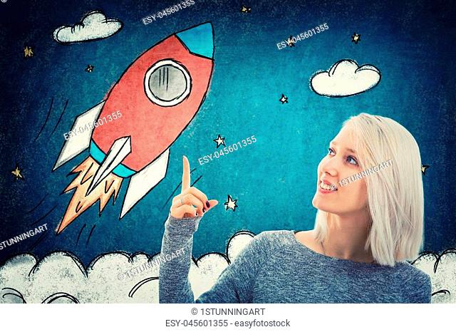 Portrait of smiling student girl pointing her finger up, showing a drawn rocket ship take off in space. Business launch and development