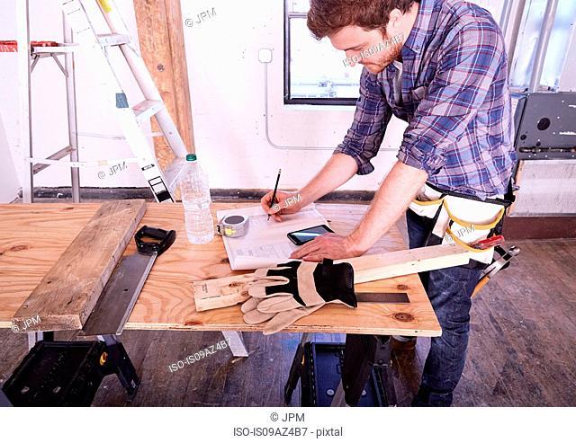 Carpenter in workshop writing in notebook
