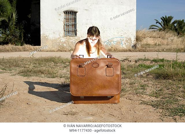 Woman opening an abandoned suitcase