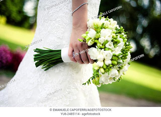 Detail of the hands of bride with bouquet of flowers