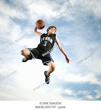 Caucasian teenager playing basketball