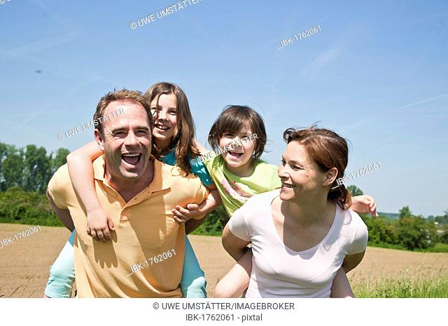 Mother and father carrying their children piggyback across a field