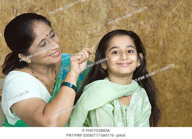 Mature woman combing hair of her granddaughter