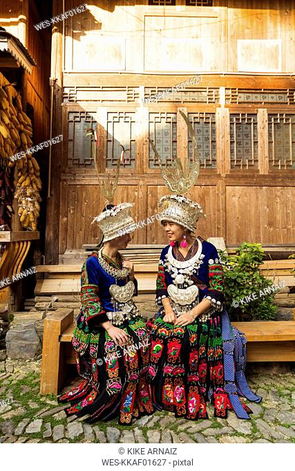 China, Guizhou, two smiling young Miao women wearing traditional dresses and headdresses