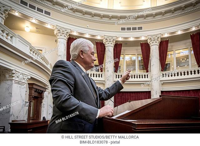 Caucasian politician giving speech in capitol building