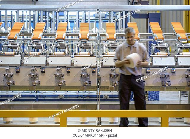 Workers examining thread in textile mill