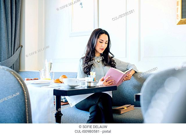 Young woman reading book whilst having champagne breakfast at boutique hotel in Italy
