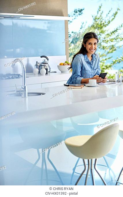 Portrait smiling woman using cell phone at kitchen counter