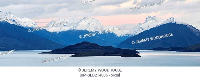 Snowcapped mountains and island near remote lake, Queenstown, Central Otago, New Zealand