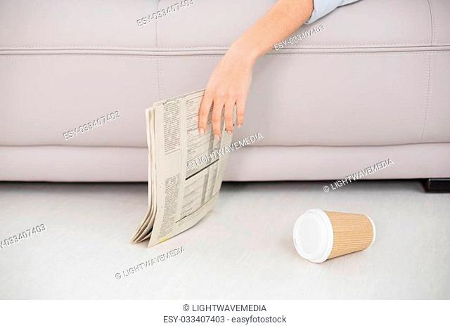 Mid section of an asleep woman holding newspaper on sofa at home