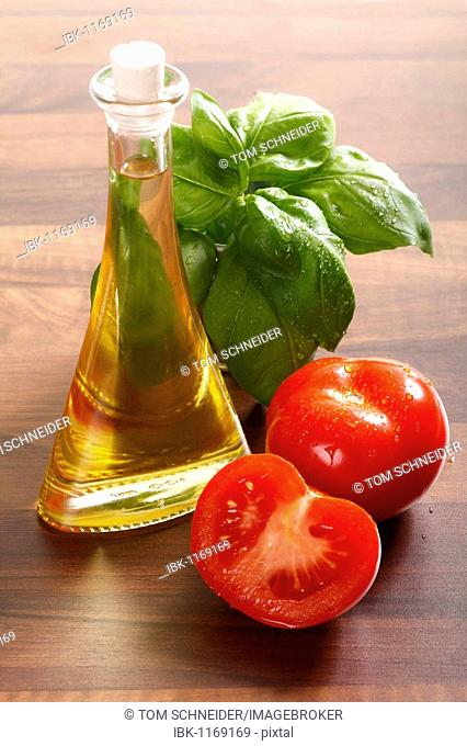 Tomatoes, olive oil and fresh basil on a wooden table