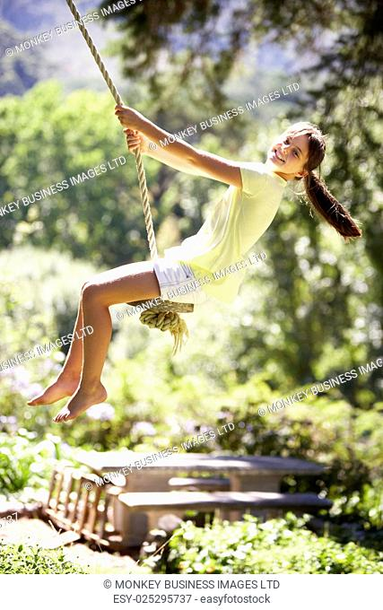 Young Girl Having Fun On Rope Swing