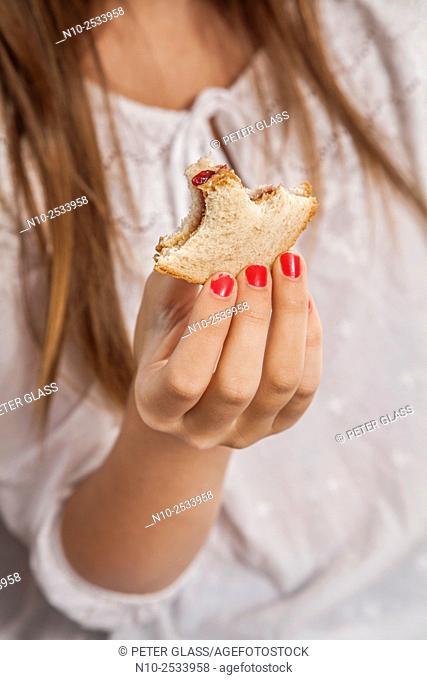 Teenage girl eating a sandwich
