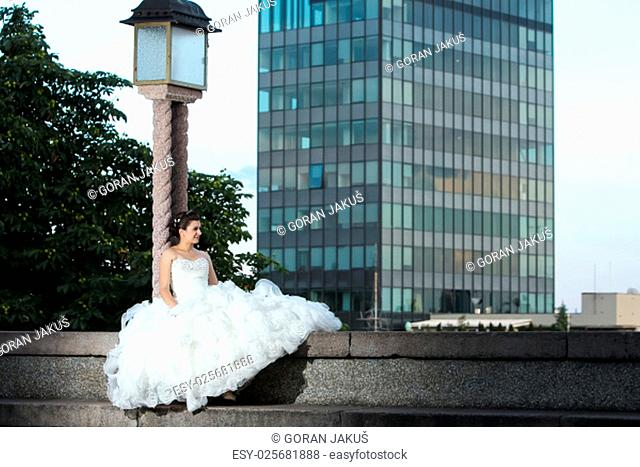 A bride sitting on a concrete wall, leaning on a street lamp and looking away with a skyscraper and roofs of Zagreb in the background