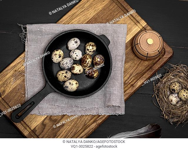raw quail eggs in the shell lie in a black cast-iron frying pan, top view