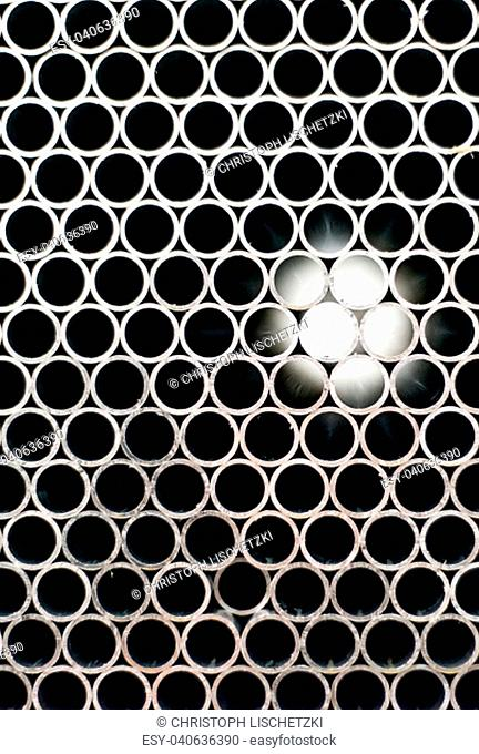 Abstract image of metal pipes showing light on the other end. Background texture