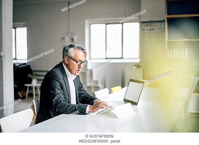 Senior businessman using tablet at table