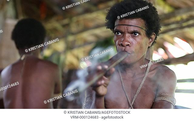 Kombai woman smoking a pipe, Papua, Indonesia, Southeast Asia