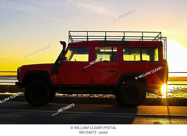 A red landrover silhouetted in the sunset