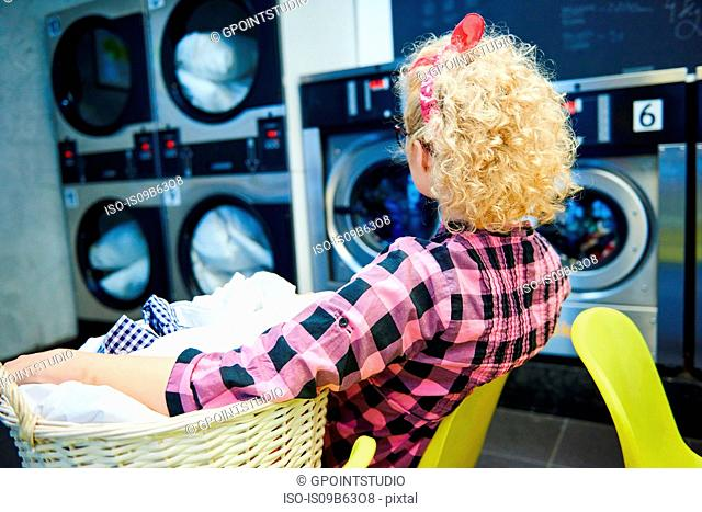 Woman watching washing machines in laundrette