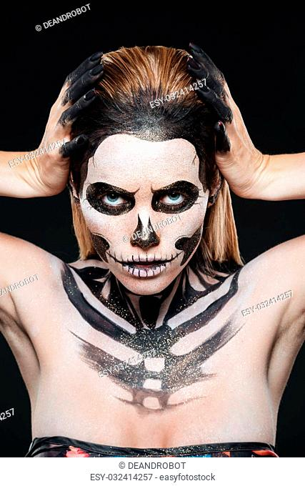 Woman with skeleton halloween makeup over black background