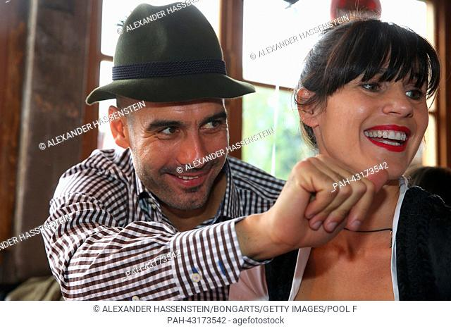 Pep Guardiola, head coach of Bayern Muenchen, and his wife Cristina Guardiola pictured during the Oktoberfest 2013 beer festival at Kaefers Wiesenschaenke in...