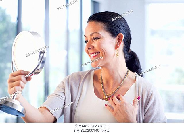 Hispanic woman trying on jewelry in store