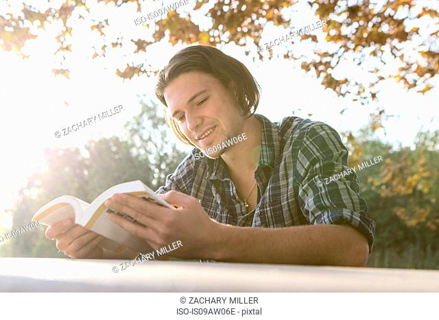 Young man outdoors sitting at table looking down reading book, smiling