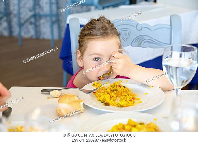 four years old blonde girl eating Spanish paella rice with spoon from white plate, sitting in restaurant. Funny portrait looking at camera