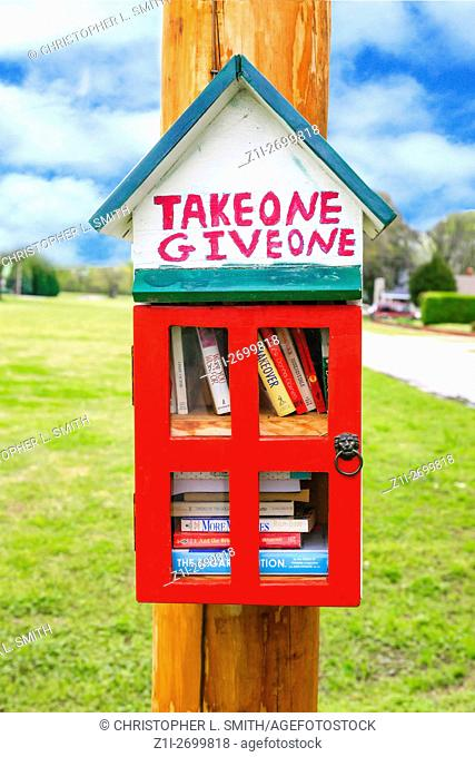 Take One, Give One, Birdhouse style free lending library on an electricity pole in a suburb of Tucumbia, AL