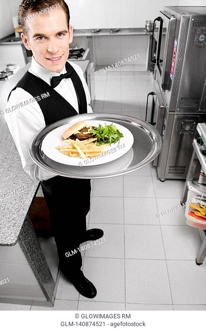 Portrait of a waiter holding a tray of snacks