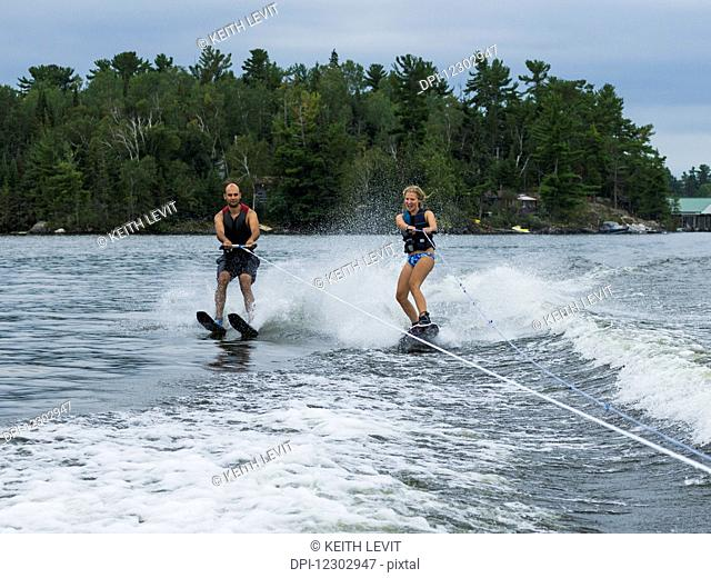 A young couple waterskiing side by side on a lake; Ontario, Canada