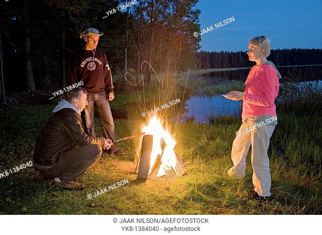 Hikers Companion by Campfire near Water in Night